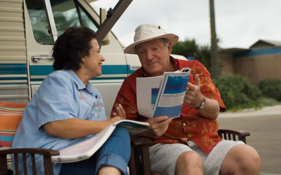 Image of two people with magazines used to depict Medigap versus Medicare Advantage. Talking and comparing.
