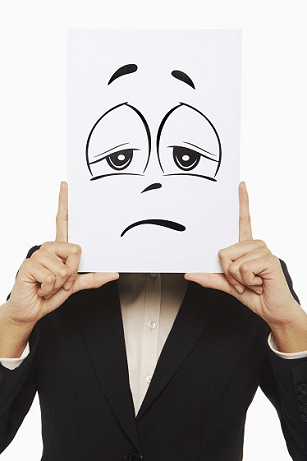 Person holding a drawing of a sad face depicting sadness due to Medicare no longer have zero deductible Medigap plans.