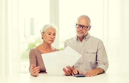 senior couple with papers trying to determine if they need to sign up for Medicare