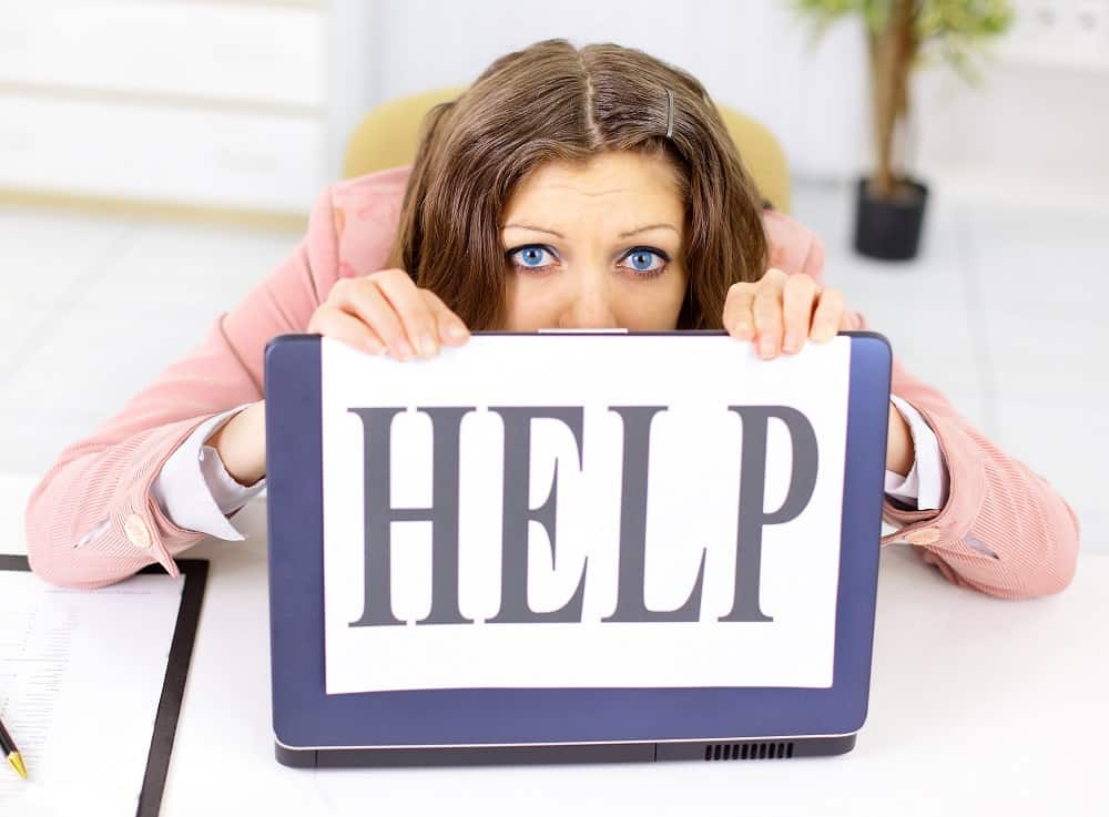 Image of woman holding help sign.